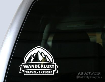 Wanderlust: Travel, Explore Decal (Badge with Mountains) in White (shown on truck window)