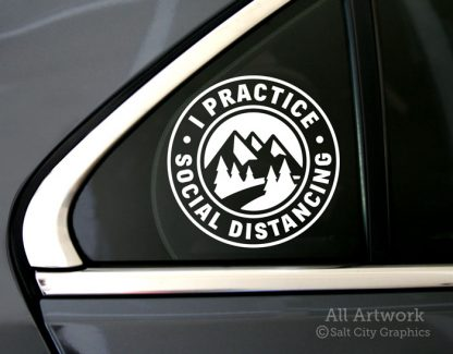 I Practice Social Distancing decal in White with pine trees and mountains (shown on car window)