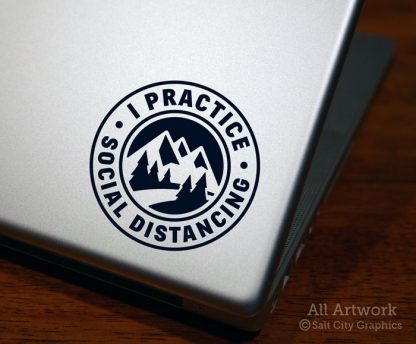 I Practice Social Distancing decal in Black with pine trees and mountains (shown on laptop)